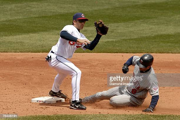 Base runner Nick Punto of the Minnesota Twins steals second base as shortstop Mike Rouse of the Cleveland Indians takes a throw from Victor Martinez...