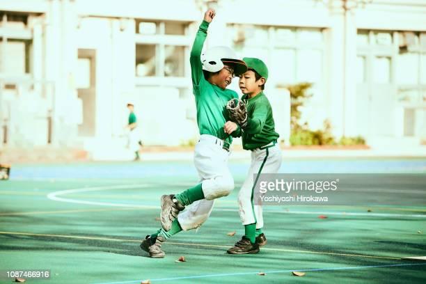 Base runner running between base, fielder catching ball in baseball game