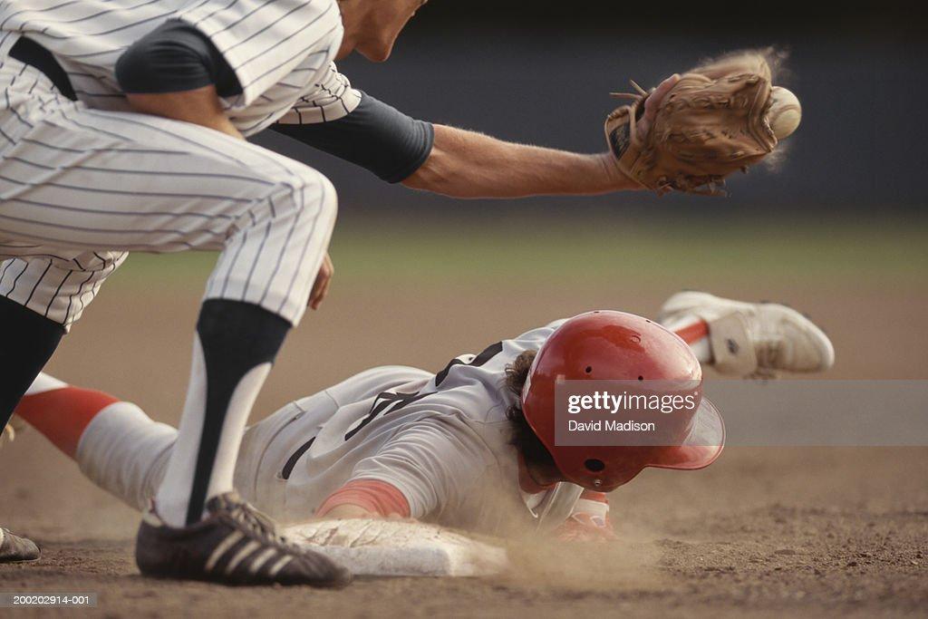 Base runner sliding into base, fielder catching ball in baseball game : Stock Photo