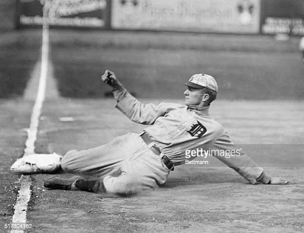 Baseball. A stationary action shot of Ty Cobb sliding. Note the flapping long sleeves and the turned up collar of the old time uniform. The base is...