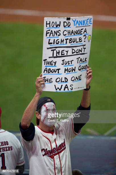 ALDS Playoffs Cleveland Indians fan with face painted and holding up sign in stands that reads HOW DO YANKEE FANS CHANGE A LIGHT BULB THEY DON'T THEY...