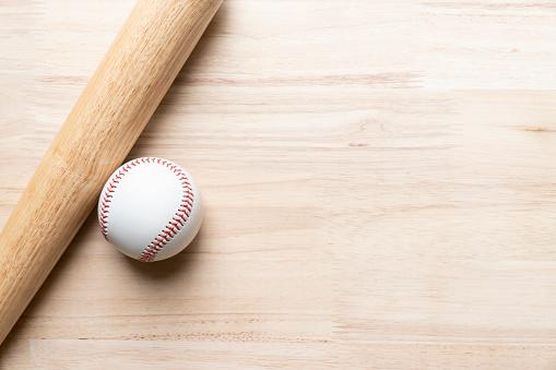 baseball and baseball bat on wooden table background, close up 972355224