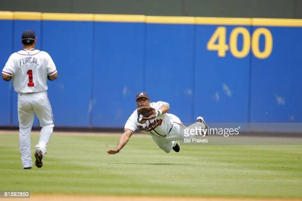 Baseball Atlanta Braves Andruw Jones in action diving and fielding catch vs Pittsburgh Pirates Atlanta GA 7/22/2004