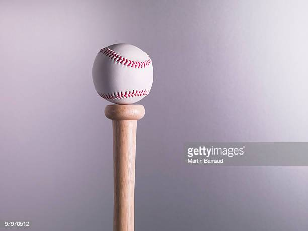 baseball balancing on bat - things that go together stock photos and pictures