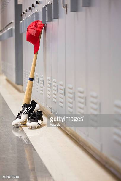 Baseball bat and clothing by lockers