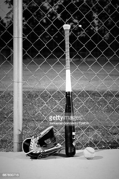 Baseball Bat And Glove By Chainlink Fence At Dusk