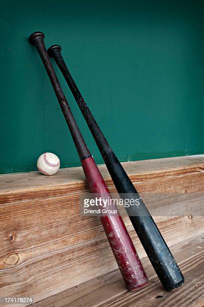 Baseball bats and ball on the dugout bench.