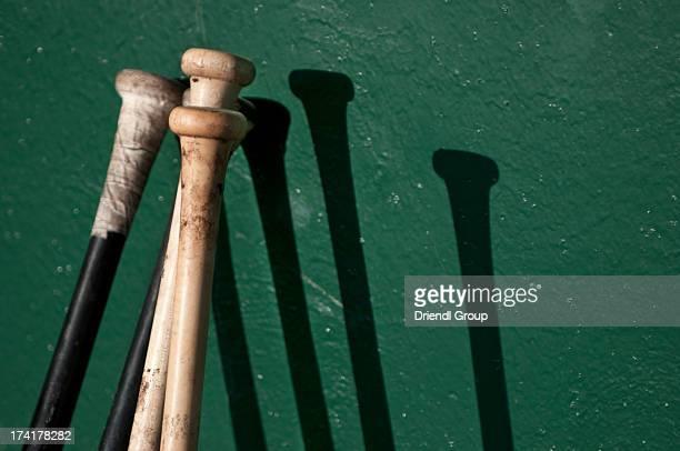 baseball bats making shadows on dugout wall. - dugout fotografías e imágenes de stock