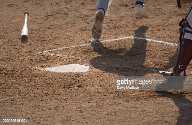 Baseball batter dropping bat, running from home plate, low section