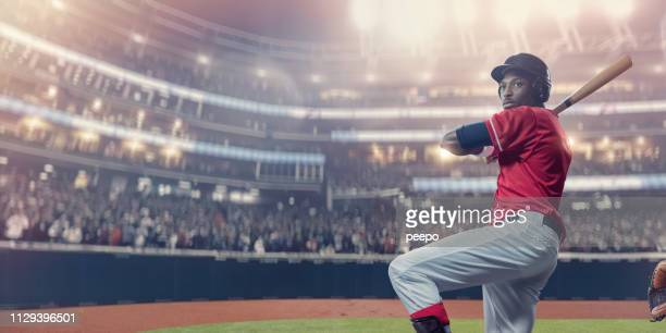 baseball batter stands ready for ball during arena baseball game - baseball player stock pictures, royalty-free photos & images
