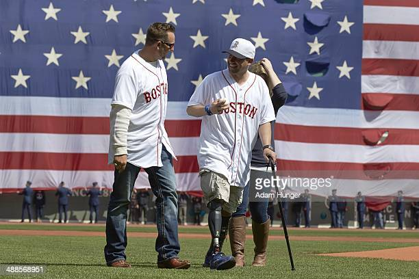 Boston Marathon bombing survivor Marc Fucarile with former Boston Red Sox player Kevin Millar on field before Boston Red Sox vs Baltimore Orioles...
