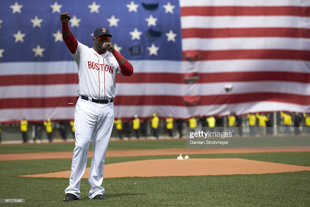 Boston Red Sox David Ortiz (34) addressing the crowd on field before game vs Kansas City Royals at Fenway Park. A ceremony was held before the game in remembrance of the victims of the 4/15/13 Boston Marathon Bombings. View of American flag draped over Green Monster. Damian Strohmeyer F143 )