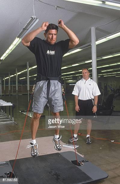Baseball Boston Red Sox Nomar Garciaparra with trainer Mark Vestergen demonstrating vertimax jump exercise during preseason workout at Athletes'...
