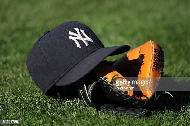 A baseball cap and a glove belonging to the New York Yankees sits on the field during batting practice before the game against the Oakland Athletics...