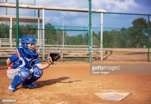 baseball catcher crouching on field - baseball catcher stock photos and pictures