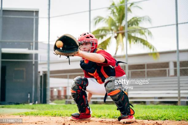 baseball catcher crouching to catch pitch in center of mitt - caneleira roupa desportiva de proteção imagens e fotografias de stock