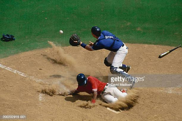 baseball catcher fielding ball as base runner slides into home - baseball player stock pictures, royalty-free photos & images