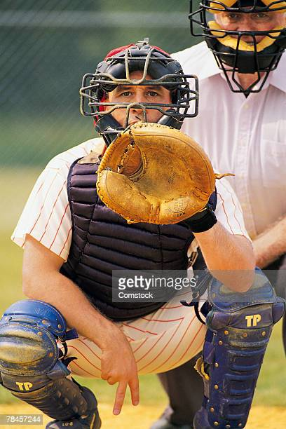 baseball catcher signals pitch - baseball catcher stock photos and pictures