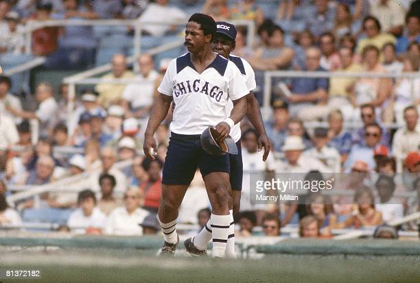 Baseball Chicago White Sox Ralph Garr held at 1st base with teammate Minnie Monoso as coach during game vs Baltimore Orioles Sox wearing shorts with...