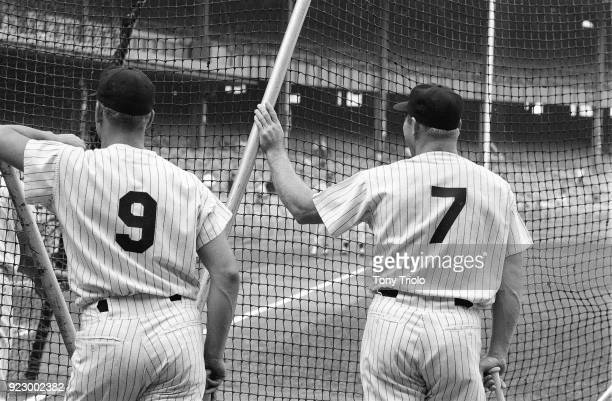 Closeup from rear of New York Yankees Roger Maris and Mickey Mantle looking on during batting practice before game vs Los Angeles Angels at Yankee...