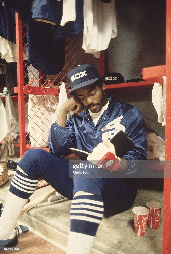 Closeup of Chicago White Sox Chet Lemon reading a book in locker