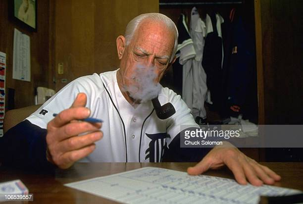 Closeup portrait of Detroit Tigers manager Sparky Anderson filling out lineup cards and smoking pipe in his office before game vs California Angels...