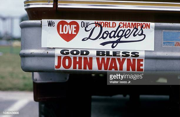 Closeup view of bumper stickers on car that reads WE LOVE OUR WORLD CHAMPION DODGERS and GOD BLESS JOHN WAYNE in Dodgertown Vero Beach FL 4/10/1982...