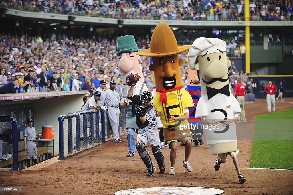 Colorado Rockies Paul Phillips (39) trying to avoid mascots (L-R) Paco the Chorizo, Brett Wurst the Bratwurst, and Guido the Italian Sausage on field during sausage race at Milwaukee Brewers game. Milwaukee, WI 6/11/2009