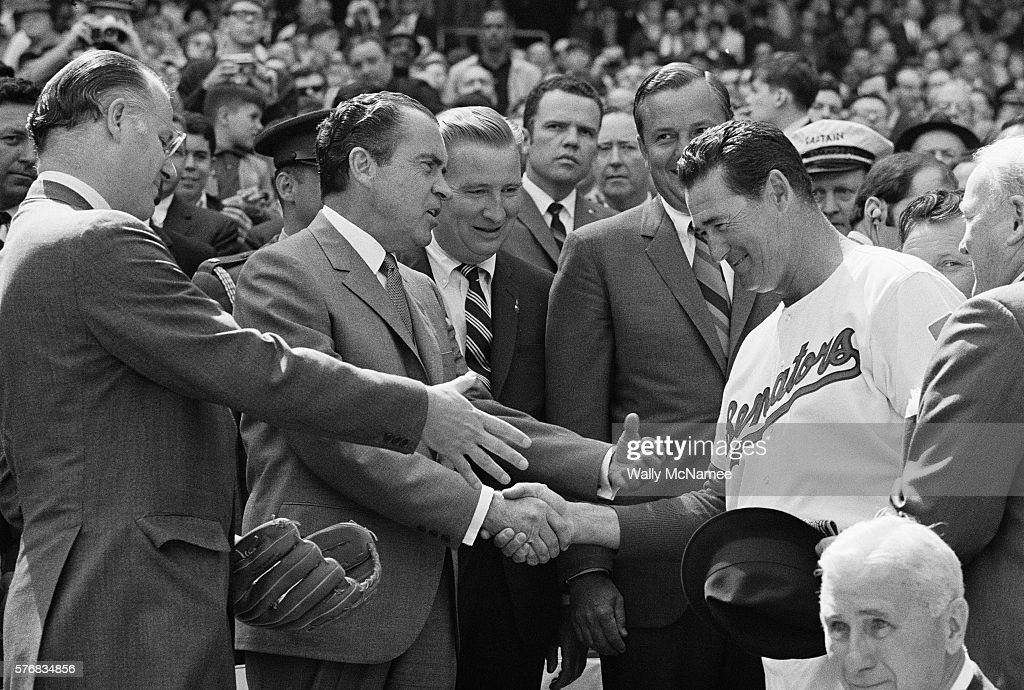 Baseball Commissioner Bowie Kuhn holds out his hand as President Richard Nixon shakes hands with Ted Williams. Former Senators pitcher Sid Hudson stands next to team manager Ted Williams and Washington Senators team owner Robert Short stands next to President Nixon.