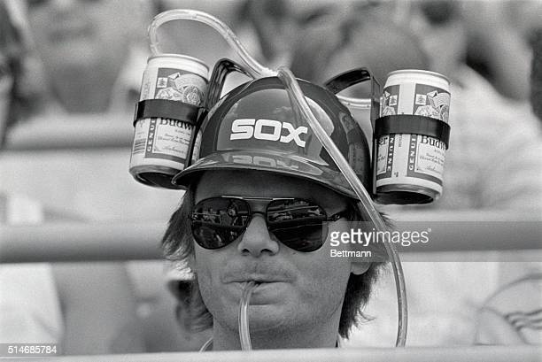 Baseball fan Donald Puster drinks his beer from a contraption attached to his baseball cap It features two cans of beer and a drinking tube that is...