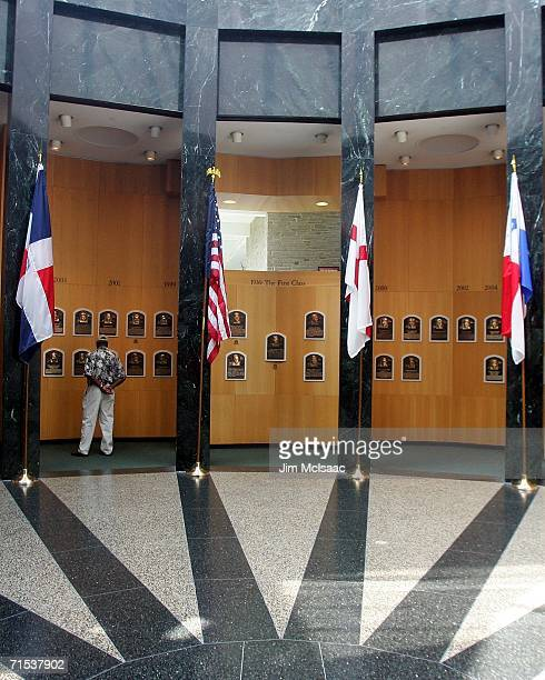 A baseball fan looks at the plaques of players inducted into the National Baseball Hall of Fame and Museum during the Baseball Hall of Fame weekend...