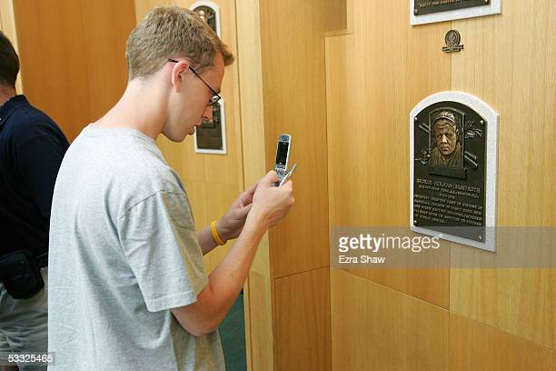 Baseball fan photographs commemorative plaques with his cell phone at the induciton of 38 new members to the the National Baseball Hall of Fame and...