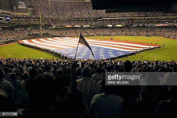 A baseball fan waves a small national flag while a large US flag is unvieled on the field during ceremonies before the start of Game 2 of the 2001...