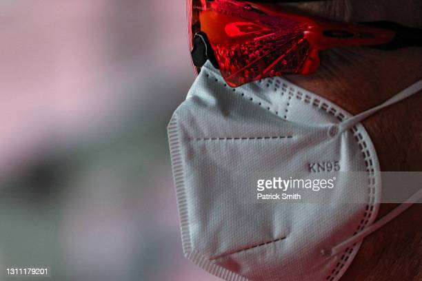 Baseball fan wears a KN95 protective face covering due to the coronavirus as a baseball diamond is reflected in their sunglasses as the Washington...