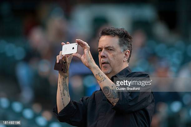 A baseball fan with a picture of a NIkon camera tattooed onto his elbow shoots an image with an iPhone before a game between the Colorado Rockies and...