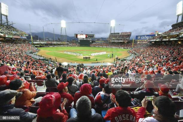 Baseball fans cheer before the start of a seasonopening game between the Hiroshima Carp and the Hanshin Tigers at Mazda Stadium in the western Japan...