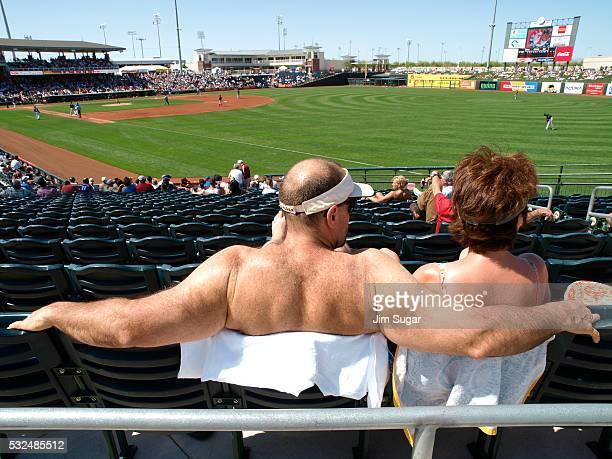 Baseball fans soak in the sun during spring training major league baseball action between the San Francisco Giants and Texas Rangers