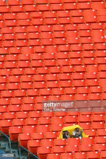 Baseball Fans watching the Florida Marlins play the Cincinnati Reds cover up during a rain shower at Pro Player Stadium on June 1 2003 in Miami...