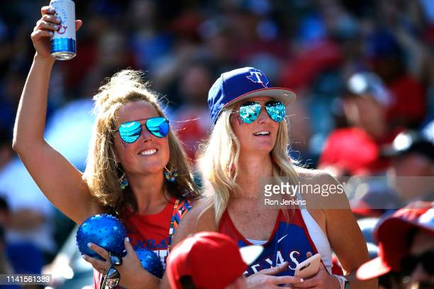 Baseball fans wave and smile at friends during the game between the Toronto Blue Jays and the Texas Rangers during the seventh inning that Globe Life...