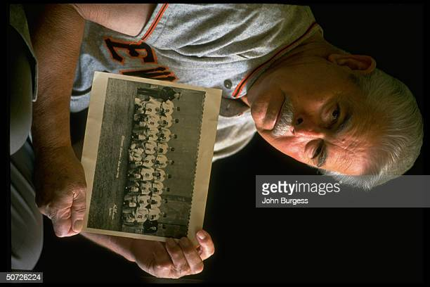 Feature. Portrait of former Spokane Indians player Jack Lucky Lohrke alone, holding photo of 1946 Indians.; Nine members of the 1946 team died in a...