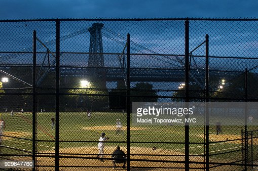 Baseball field in Manhattan with a view of Williamsburg Bridge behind during evening.
