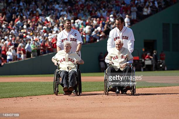 Former Boston Red Sox players Jason Varitek with Johnny Pesky in wheelchair and Tim Wakefield with Bobby Doerr in wheelchair during 100th anniversary...