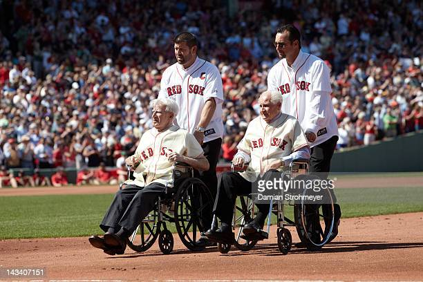 Former Boston Red Sox players Jason Varitek with Johnny Pesky on wheelchair and Tim Wakefield with Bobby Doerr in wheelchair during 100th anniversary...