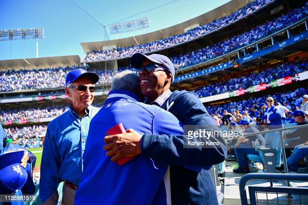 Former Los Angeles Dodgers pitcher Sandy Koufax looks on as Lou Johnson embraces comedian Arsenio Hall on field before game vs Arizona Diamondbacks...