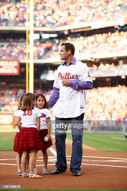 Former Philadelphia Phillies player Pat Burrell with John Vukovich 's granddaughters during ceremonial first pitch before game vs Boston Red Sox at...