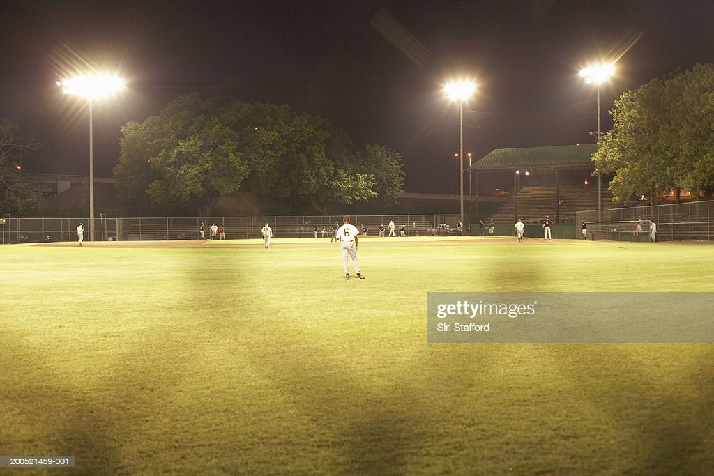 Baseball game under artificial lightning through chainlink fence : Stock Photo