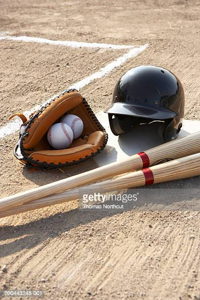 Baseball glove, balls, bats and baseball helmet at home plate