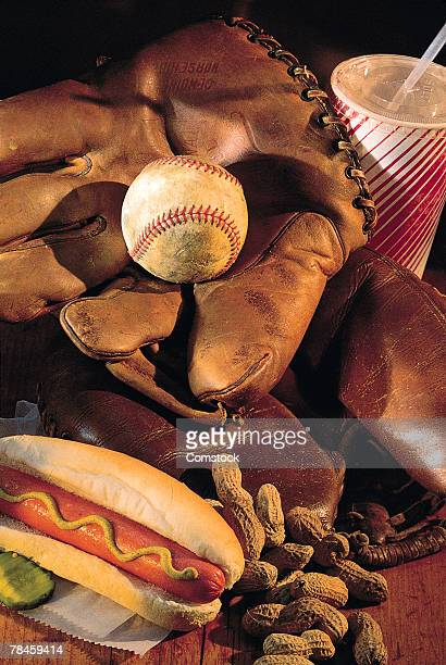 Baseball glove , hot dog , peanuts and soda