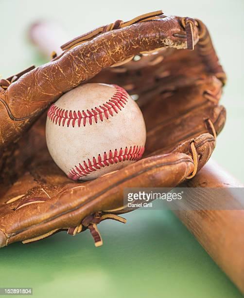 Baseball glove with ball and bat