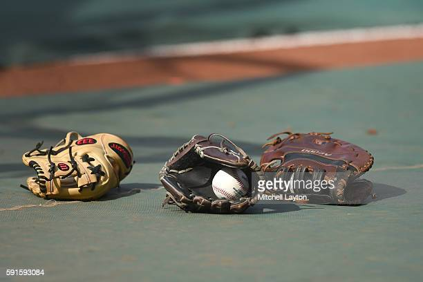 Baseball gloves sit on the field before a baseball game between the Baltimore Orioles and the Boston Red Sox at Oriole Park at Camden Yards at on...